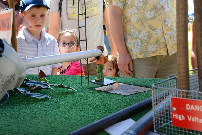 PETERSON AIR FORCE BASE, Colo. – Attendees learn about electric power line dangers from volunteers at the Colorado Springs Utilities booth during STEM Rocks! at the Peterson Air and Space Museum Aug. 23. The volunteers wanted children and parents alike to practice safety near power lines as the human body is an excellent conductor of electricity. Children and parents could visit nearly 30 booths to learn about Science, Technology, Engineering and Math in a fun, carnival-like environment. (U.S. Air Force photo/Tech. Sgt. Jared Marquis)
