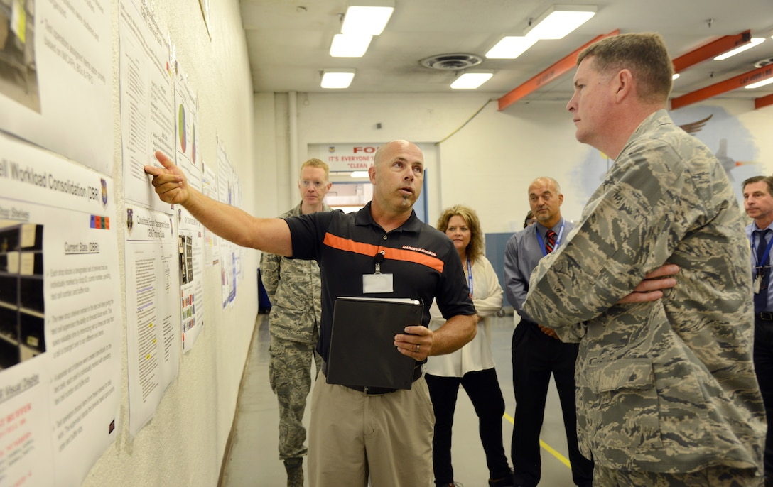 "Mike Comfort, the 550th Commodities Maintenance Squadron's Stock Record Account Number manager, briefs Oklahoma City Air Logistics Complex Commander Brig. Gen. Gene Kirkland about the development of the Consolidated Engine Management System Training guide and how it has been an effective process improvement in their area. During General Kirkland's ""Walk the Wall"" visit to the Cruise Missile Shop, other members of the 76th Commodities Maintenance Group also briefed the general about how they have implemented processes promoting the AFSC Way into their daily work routines and how it has positively impacted their workflow. (Air Force photo by Kelly White)"