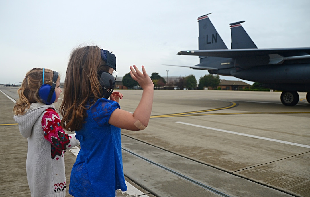 Children wave to 494th Fighter Squadron F-15E Strike Eagle fighter pilots as they arrive at Royal Air Force Lakenheath, England, Aug. 25, 2014, from exercises in the U.S. The 48th Fighter Wing aircraft returned after participating in Red Flag exercise 14N-3 at Nellis Air Force Base, Nev., and Combat Hammer and Combat Archer exercises at Hill Air Force Base, Utah. (U.S. Air Force photo by Airman 1st Class Erin O'Shea/Released)