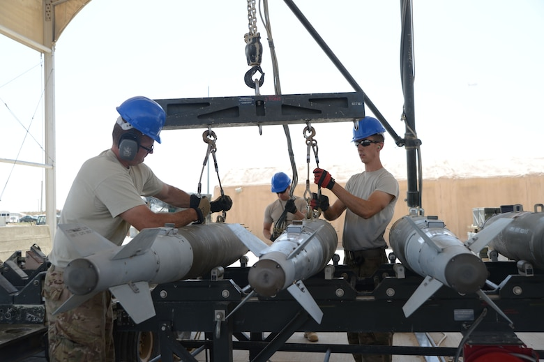 Tech. Sgt. Patrick Williams (left) and Senior Airman Brandon Graves attach GBU-38 bombs to a hoist that will be used with a munitions assembly conveyer to move the bombs during transport Aug. 14, 2014, at Bagram Airfield in support of Operation Enduring Freedom.  Both men are currently assigned to the 455th Expeditionary Maintenance Squadron and both are reservists deployed from the 442nd Fighter Wing, Whiteman Air Force Base, Mo. (U.S. Air Force photo by Master Sgt. Cohen A. Young)