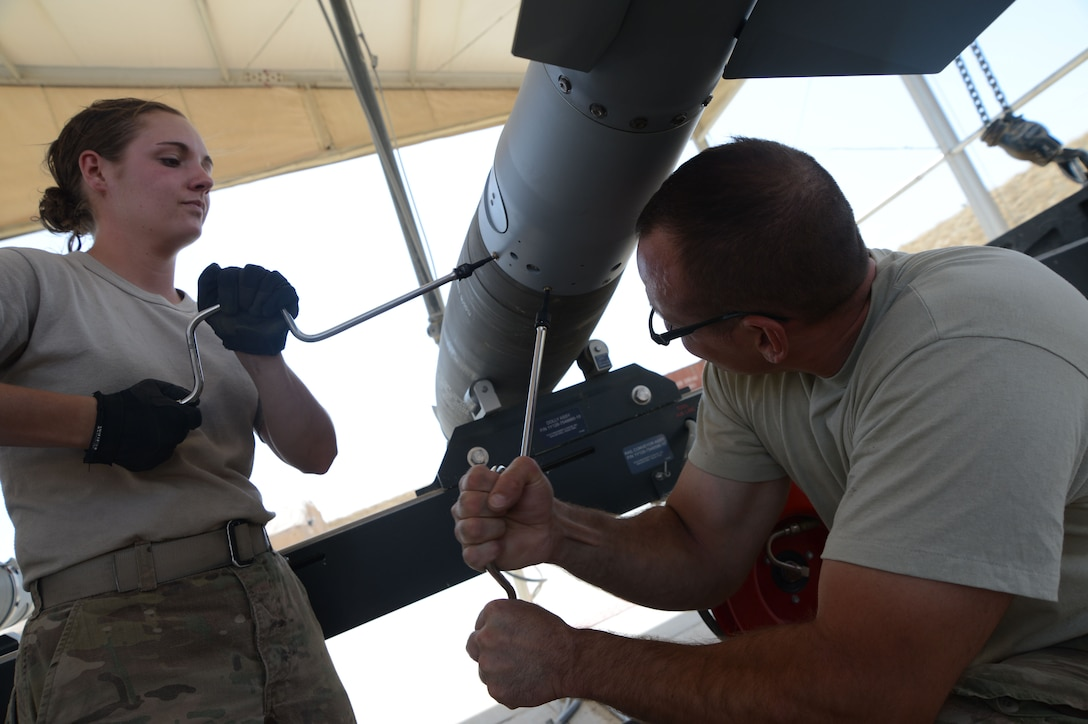 Airman 1st Class Casey Cain and Tech. Sgt. Patrick Williams tighten the screws on a GBU-38 during its construction while at Bagram Airfield, Afghanistan Aug. 14, 2014. The GBU-38 is a necessary part of the weapon system of the F-16C Fighting Falcon. Cain is a reservist  deployed from Whiteman Air Force Base, Mo. Williams is a reservist deployed from the 442nd Fighter Wing in Missouri. (U.S. Air Force photo by Master Sgt. Cohen A. Young)