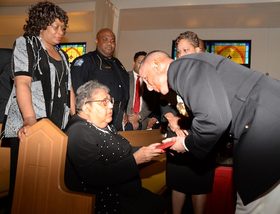 Carletha Windom accepts a proclamation honoring her late husband, Pfc. James Windom - an original Montford Point Marine - from Col. Don Davis, commanding officer, Marine Corps Logistics Base Albany, during a ceremony at the Chapel of the Good Shepherd, here, Aug. 22.