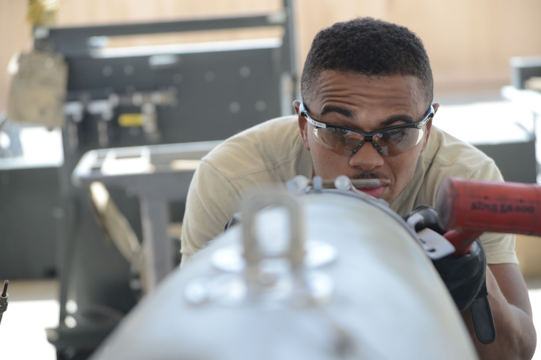 Airman 1st Class Tony Chatman aligns the front strike of the bomb lugs on a GBU-38 bomb Aug. 14, 2014, at Bagram Airfield, Afghanistan. The GBU-38 is the prime bomb utilized with the F-16C Fighting Falcon. Chatman is a munitions systems technician assigned to the 455th Expeditionary Maintenance Squadron and is a native of Atlantic City, N.J. (U.S. Air Force photo/Master Sgt. Cohen A. Young)