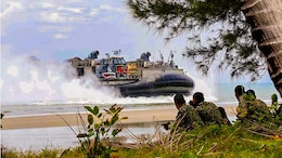Members of the Malaysian Armed Forces observe as a landing craft air cushion carrying Marines and sailors from the 11th Marine Expeditionary Unit and Amphibious Squadron Five arrives on a beach during Malaysia-United States Amphibious Exercise 2014. MALUS AMPHEX 14 is a bilateral exercise between the 11th MEU and Malaysian Armed Forces that includes operational and tactical level training in planning, command and control, and combat service support using both ground and sea assets.