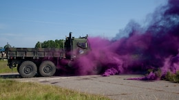 A simulated improvised explosive device is set off as a tactical convoy travels down a simulated highway during the Autonomous Mobility Applique System Joint Capability Technology Demonstration Aug. 20, 2014, at the Savannah River Site in Aiken, South Carolina. The IED demonstration tested the AMAS' capability to detect obstacles to better maneuver a convoy.