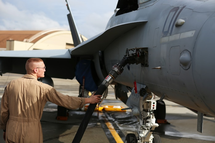 Sgt. Samuel Riley, a fixed-wing aircraft mechanic with Marine Fighter Attack Squadron 122, checks to make sure fuel is flowing to an F/A-18 C Hornet aboard Eielson Air Force Base, Alaska, August 25, 2014. Riley and a crew of Marines prepared the Hornet for its first flight in Alaska. While at Eielson, VMFA-122 is scheduled to conduct unit level training and fly with squadrons from the United States Air Force to enhance interoperability between services.