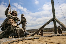 A recruit from Mike Company, 3rd Recruit Training Battalion, attempts to swing to a platform during Gonzalez's Challenge at Marine Corps Base Camp Pendleton, Calif., Aug. 20. Gonzalez's Challenge is one of many exercises recruits are required to perform during the Crucible, a 54-hour exercise that is the final test of recruit training.