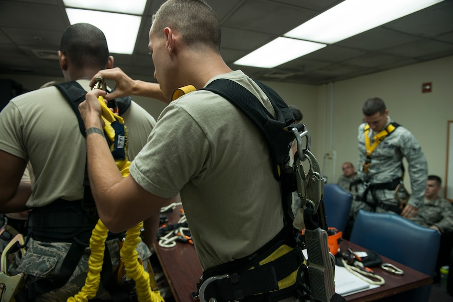 Senior Airman Charlie Hegwer, a 51st Communications Squadron cable and antenna technician, checks one of his student's equipment Aug. 27, 2014, at Osan Air Base, Republic of Korea. Prior to going to an on-site climb, the students must personally test all of their equipment to ensure safety. (U.S. Air Force photo by Staff Sgt. Jake Barreiro/Released)