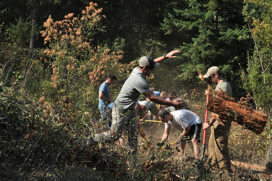 Airmen from the 22nd Training Squadron clear trail paths with family and friends as part of their resiliency and team-building activity on Tubbs Hill in Coeur d'Alene, Idaho, August 11, 2014. A team of about 30 volunteers from the 22nd TRS and SERE Solutions Inc., along with family friends, participated in a two day team building and resiliency event that ended with an overnight stay at a local campground, followed by a 15 mile bike ride down the historic Hiawatha Trail in Wallace, Idaho, that crosses the Montana border.  (U.S. Air Force photo by Staff Sgt. Alexandre Montes/Released)