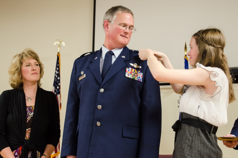 The wife of Lt. Col. David J. Mounkes watches as their daughter pins new rank insignia on his uniform during a ceremony promoting Mounkes to the rank of colonel at the Kentucky Air National Guard Base in Louisville, Ky., July 12, 2104. Mounkes, the outgoing commander of the 123rd Global Mobility Squadron, also took command of the Kentucky Air Guard's 123rd Contingency Response Group the same day. (U.S. Air National Guard photo by Senior Airman Joshua Horton)