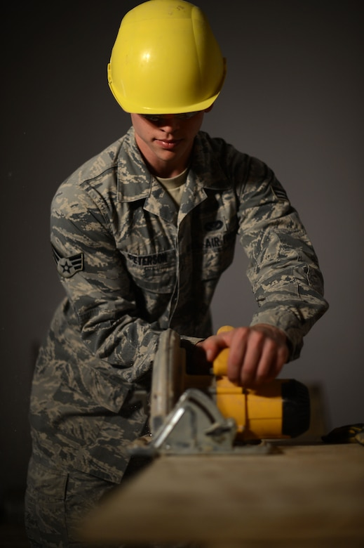 U.S. Air Force Senior Airman Dylan Peterson, a 52nd Civil Engineer Squadron structures technician from Fargo, N.D., saws a sheet of wood at a construction site inside the Skelton Memorial Fitness Center Aug. 26, 2014. The state-of-the-art combat fitness gym may house more than 150 people and support more than 20 classes a week upon its completion. (U.S. Air Force photo by Senior Airman Gustavo Castillo/Released)