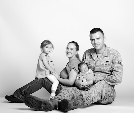 Senior Airman Paul Stewart, 509th Maintenance Squadron low observable structural maintainer, and his wife Lindsey, pose with their daughters Anna (left), and Emily (right). On July 20, 2014, Stewart delivered his and his wife's second daughter, Emily, when they were unable to make it to the hospital in time. (U.S. Air Force photo by Airman 1st Class Joel Pfiester/Released)
