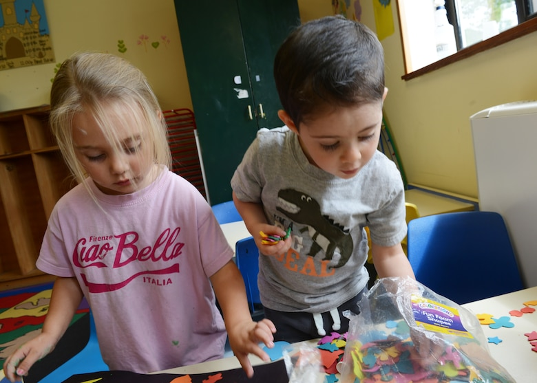 Mirabelle Heiser and Marshall Lambert play with fun foam shapes during arts and crafts time, Aug. 25, 2014, at the Aviano Co-op Care program at Aviano Air Base, Italy. The Co-op is open from 9 a.m. to 12 p.m. from Monday to Friday to allow parents to run errands or study for school. (U.S. Air Force photo/Airman 1st Class Ryan Conroy)