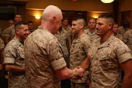 Sergeants Philip Kelly (Near) and Derrek Cardinale (Far), receive Navy and Marine Corps Achievement Medals from Lt. Gen. Richard P. Mills, commander of Marine Forces Reserve, for their work as Lance Corporal Leadership Ethics Seminar trainers after educating senior enlisted advisors in the Marine Corps Support Facility New Orleans auditorium, Aug. 27, 2014. The train-the-trainer course was designed to inform senior enlisted advisors on the new Lance Corporal Leadership Ethics Seminar implemented throughout the Marine Corps. The seminar was implemented to inform lance corporals of the resources available to them, as well as motivate them to succeed and strive for the next rank.
