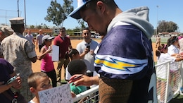 Manti Te'o, a San Diego Chargers' linebacker, signs an autograph for a child during a military appreciation day aboard Marine Corps Air Station Miramar, Calif., Aug. 27. The Chargers practiced with the MCAS Miramar Falcons before socializing with fans.