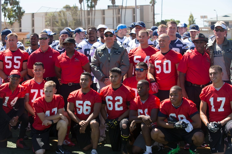 Members of the Marine Corps Air Station Miramar Falcons take a photo with the San Diego Chargers during a military appreciation day aboard MCAS Miramar, Calif., Aug. 27. The Chargers showed their support to Service members by engaging with fans and signing autographs after practice.