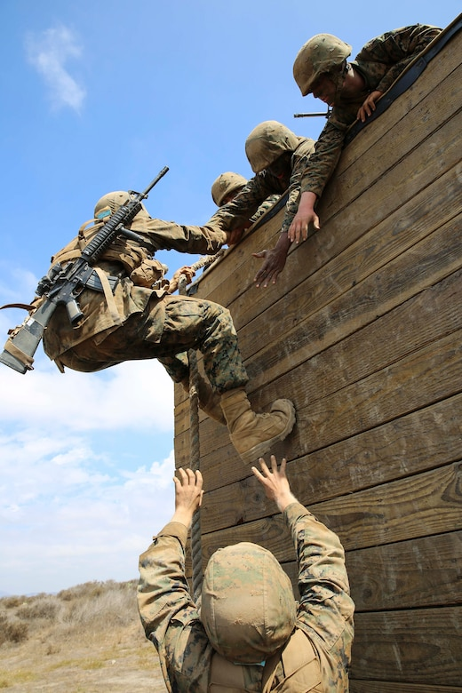 Recruits of Mike Company, 3rd Recruit Training Battalion, assist a fellow recruit climb a wall during Gonzalez's Challenge at Marine Corps Base Camp Pendleton, Calif., Aug. 20. Gonzalez's Challenge, is a two part exercise designed to promote teamwork.