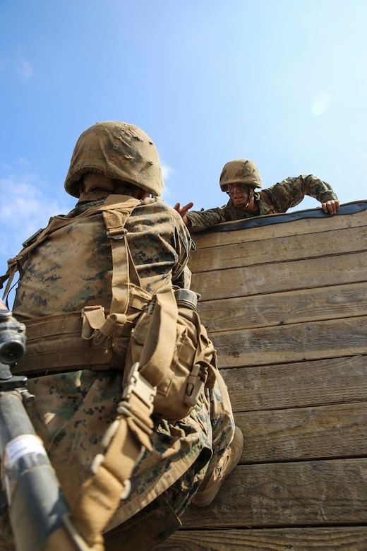 A recruit of Mike Company, 3rd Recruit Training Battalion, helps a fellow recruit climb a wall during Gonzalez's Challenge at Marine Corps Base Camp Pendleton, Calif., Aug. 20. Gonzalez's Challenge, is a two part exercise designed to promote teamwork.