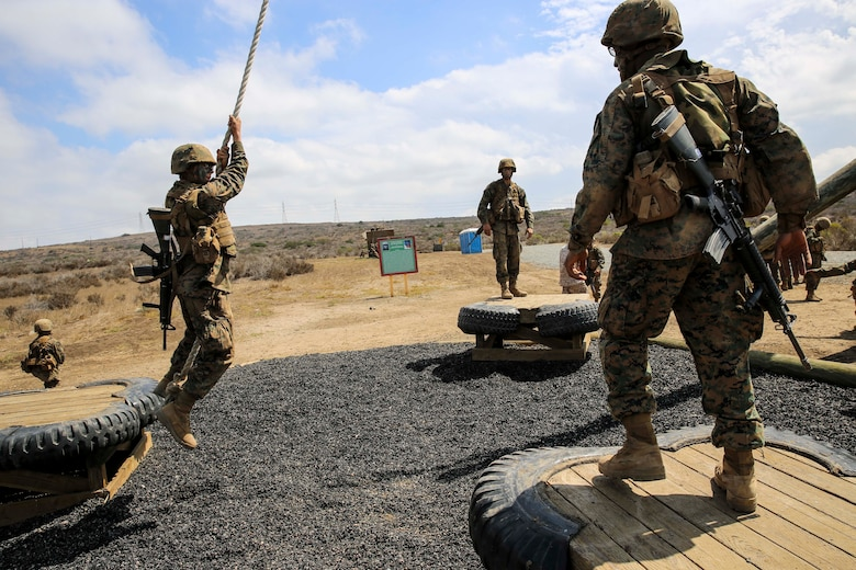 A recruit from Mike Company, 3rd Recruit Training Battalion, attempts to swing to a platform during Gonzalez's Challenge at Marine Corps Base Camp Pendleton, Calif., Aug. 20. Touching the ground marked a simulated casualty and required the recruit to perform an exercise before returning to assist his fellow recruits.
