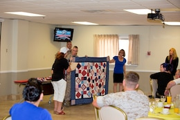Sergeant Steven B. Waddell, with Fleet Support Division, Production Plant Barstow, receives a quilt from Quilts of Valor during Quarterly Awards breakfast, Aug., 20. Quilts of Valor volunteers make quilts for deserving service members around the world.