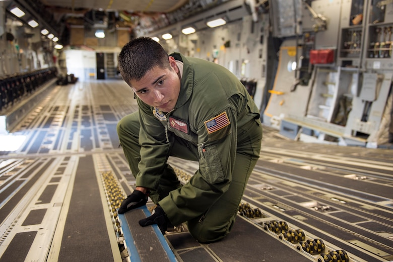 Senior Airman  Cody Nunez prepares the cargo floor for palletized cargo , Aug 25 2014.  Nunez, a loadmaster with the 21st Airlift Squadron, Travis Air Force Base, Calif., has been selected to receive the General P.K. Carlton Award for Valor for heroic activity in the medical evacuation of three Navy Seals out of Uganda.   (U.S. Air Force Photo/Heide Couch)