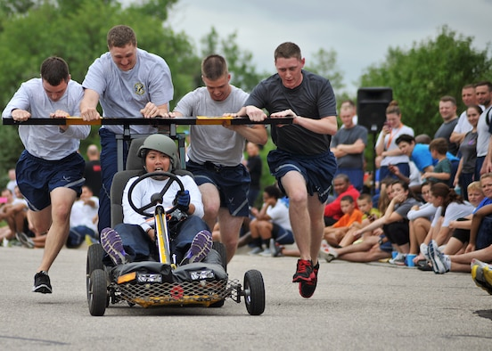 Members of the 319th Logistics Readiness Squadron push and drive toward the finish line during the Summer Bash bed race Aug. 21, 2014, on Grand Forks Air Force Base, N.D. Each team consisted of four pushers or pullers and one driver. The driver had to perform several tasks from one end of the lane in order to cross the finish line. (U.S. Air Force photo/Senior Airman Xavier Navarro)