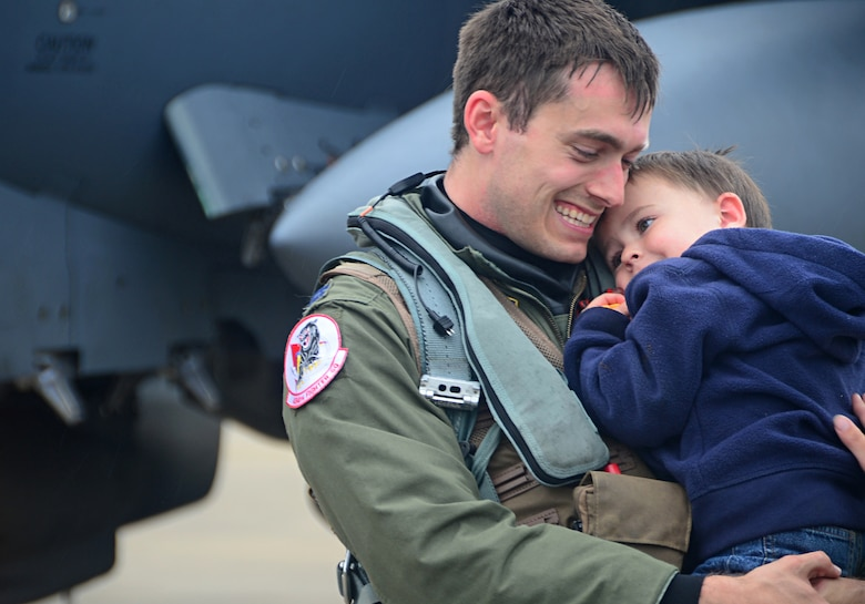 Capt. Eirk Hulme hugs his son on the flight line at Royal Air Force Lakenheath, England, Aug. 25, 2014, after returning from exercises in the U.S.  Hulme is an F-15E Strike Eagle fighter pilot with the 494th Fighter Squadron. Red Flag is an advanced training program and provides participants with valuable training in planning and executing a wide-­variety of combat missions. (U.S. Air Force photo/Airman 1st Class Erin O'Shea)