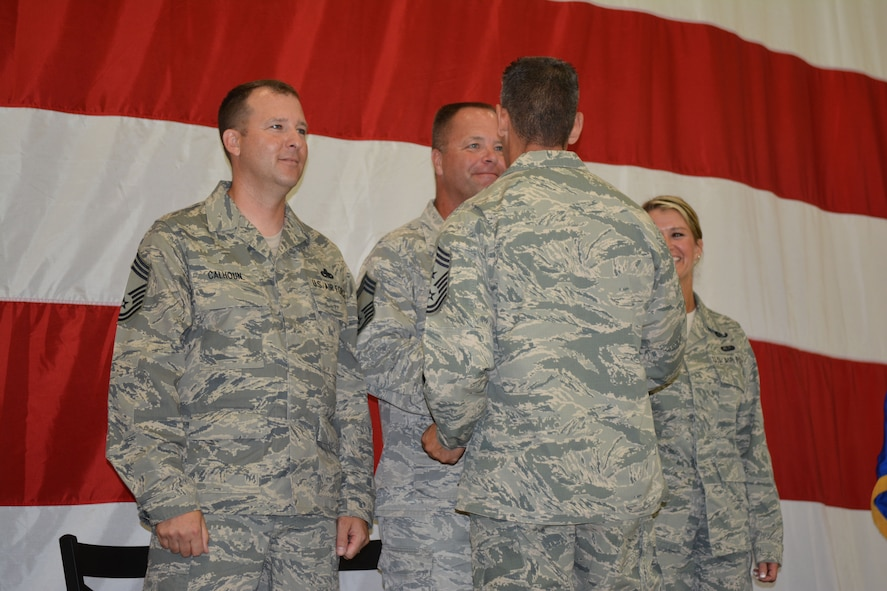 Chief Master Sgt. Thomas Safer, 115th Fighter Wing command chief, presents a state chief coin to each of the new 115 FW chiefs during their promotion recognition ceremony at Hangar 406 in Madison, Wis., Aug. 23, 2014. Only 2 percent of the Airmen in the Air National Guard can obtain the rank of chief master sergeant. (Air National Guard photo by Senior Airman Andrea F. Liechti)