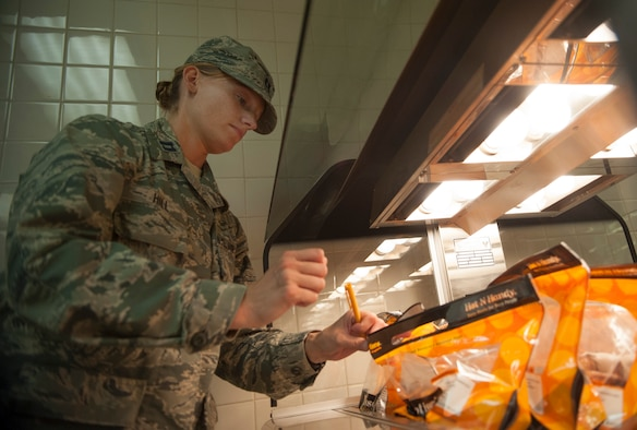 Capt. Sarah Hill, 51 Aerospace Medicine Squadron chief of public health operations, checks the internal temperature of chicken at Osan Air Base, Republic of Korea, Aug. 17, 2014. Public health makes sure that food facilities on base are following the proper U.S. food regulations. (U.S. Air Force photo by Senior Airman Matthew Lancaster/Released)