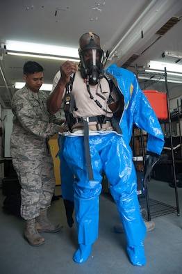 Staff Sgt. Paolo Melaendez, 51st Aerospace Medicine Squadron bioenvironmental technician, helps Tech. Sgt. Shane Polk, 51st AMDS bioenvironmental technician, put on a Level A hazardous material suit at Osan Air Base, Republic of Korea, Aug. 27, 2014. The Level A suit is the highest level hazmat protection suit against vapors, gases, mists and particles. It consists of a fully encapsulating chemical entry suit with a full-face piece self-contained breathing apparatus or a supplied air respirator with an escape cylinder. (U.S. Air Force photo by Senior Airman Matthew Lancaster/Released)