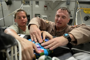 U.S. Air Force Master Sgts. Stephen Brown and Emily Edmunds attach candy to container delivery system bundles filled with fresh drinking water on a C-17 Globemaster III in preparation for a humanitarian airdrop over the area of Amirli, Iraq, Aug. 30, 2014. The candy was collected by the squadron to supplement United States' humanitarian aid. Brown and Edmunds, loadmasters, are assigned to the 816th Expeditionary Airlift Squadron. U.S. Air Force photo by Staff Sgt. Shawn Nickel
