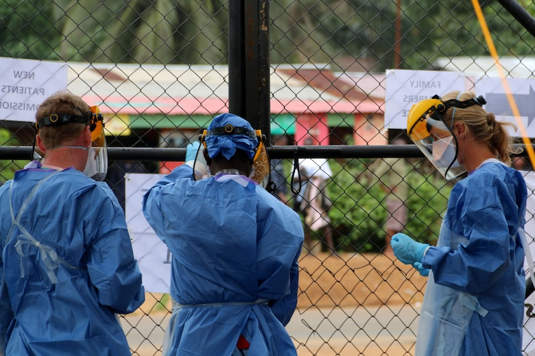 A group of health care workers hang signs on a fence at a field hospital Sept. 19, 2014, in Monrovia, Liberia. The workers are among volunteers from around the world fighting the epidemic outbreak of Ebola. (U.S. Air Force photo/Maj. Francis Obuseh)