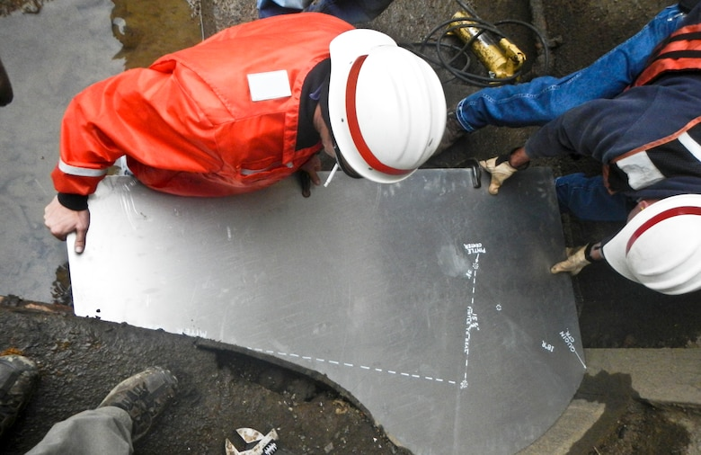 Kevin McConnell and Bob Szemanski check the shape of the miter sill using an aluminum pattern. When the repair party departed on Nov. 19, its month-plus stay yielded a more tightly sealed chamber and a more reliable facility necessary to keep navigation moving on the upper Mon.