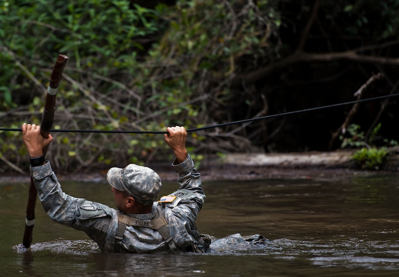 Staff Sgt. Ariel Rivera, 6th Ranger Training Battalion, crosses the river using a rope to reach a memorial on Eglin Air Force Base, Fla., for the four fallen Rangers who lost their lives Feb. 16, 1995. More than 40 Soldiers participated in the excursion Sept. 25 that followed in the footsteps of the tragic squad to learn from their experience and understand what took place that night almost 20 years ago.