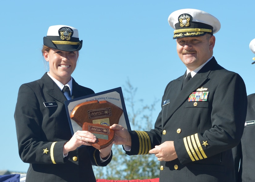 Captain Ace Van Wagoner, Commander Naval Air Forces U.S. Atlantic Fleet Force Nuclear Propulsion officer, presents Ens. Marisa Zahn with a plaque in recognition of her being named the officer class honor graduate at the Naval Nuclear Power Training Command graduation Nov. 21, 2014 at Joint Base Charleston, S.C. Van Wagoner was the guest speaker during the ceremony. (U.S. Navy photo/Petty Officer 2nd Class Jason Pastrick)