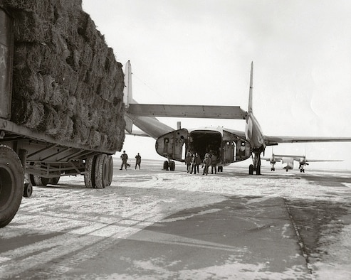 Airmen load hay onto a C-119 Flying Boxcar in December of 1964 on the runway at Malmstrom Air Force Base, Mont. Frigid temperatures and heavy snowfall during the month of December led to the declaration of a major disaster for southwest Montana. Ranchers suffered major livestock losses resulting from extreme negative temperatures and snowfall, and landowners were unable to reach their cattle and sheep.  Cargo aircraft from five reserve units were mobilized to help drop hay to the stranded animals. The Air Reserve units managed to drop 65 tons of hay to about 100,000 head of livestock during Operation Hay Lift, using low-level drops of hay bales to the stranded animals. (Courtesy photo)