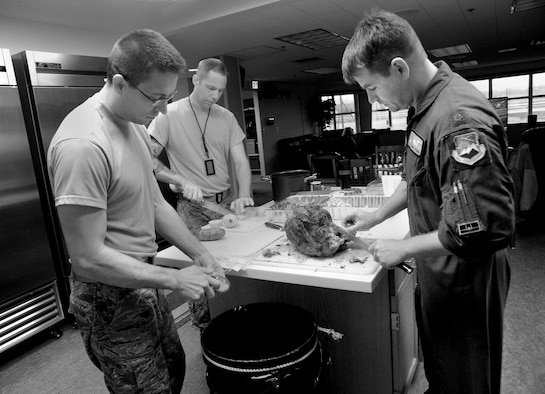 Oregon Air National Guard Maj. Bradley Young, a pilot assigned to the 123rd Fighter Squadron, 142nd Fighter Wing, Portland Air National Guard Base, Ore., cuts a Thanksgiving Turkey at the Alert Facility, as Staff Sgt. Matthew Shelburne, left, and Staff Sgt. Kyle Adair, center, prepare potatoes for dinner, Nov. 27, 2014. (U.S. Air National Guard photo by Tech. Sgt. John Hughel, 142nd Fighter Wing Public Affairs/Released)