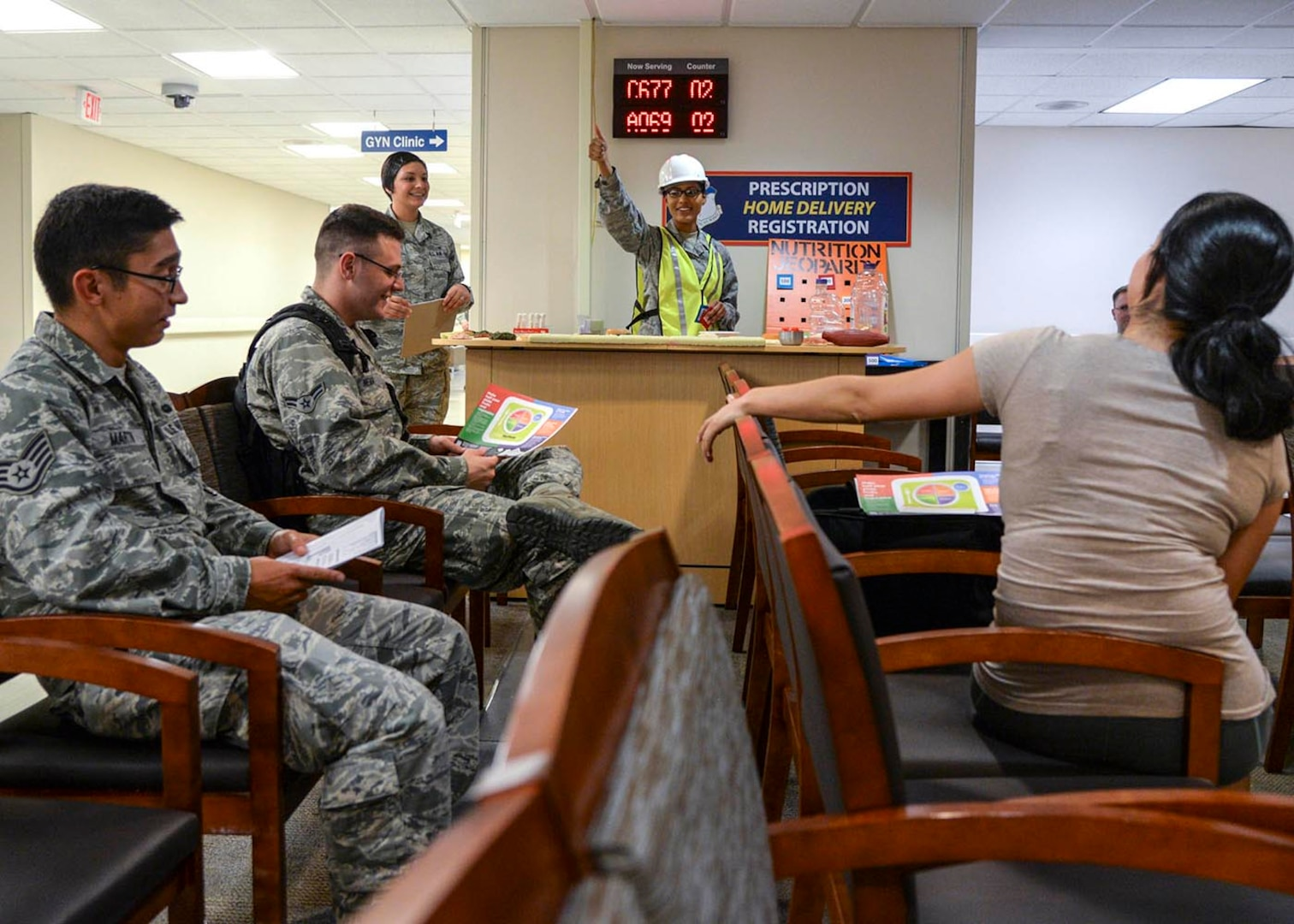 U.S. Air Force Senior Airman Catherine Scholar, 59th Medical Diagnostics and Therapeutics Squadron diet therapy journeyman, congratulates Airmen for answering correctly during a nutrition jeopardy game recently at the Wilford Hall Ambulatory Surgical Center, Joint Base San Antonio-Lackland, Texas. The event helped patients pass the time while waiting for their prescriptions, and provided them with nutritional information on foods we eat every day. (U.S. Air Force photo/Staff Sgt. Kevin Iinuma)
