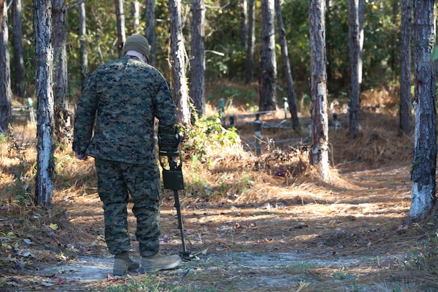 Cpl. Andrew Cochran, combat engineer, Combat Engineer Platoon, Headquarters and Service Company, Ground Combat Element Integrated Task Force, sweeps the area for simulated explosives while being observed by research monitors during a training exercise at Engineer Training Area 9 at Marine Corps Base Camp Lejeune, North Carolina, Nov. 19, 2014. (U.S. Marine Corps photo by Cpl. Paul S. Martinez/Released)