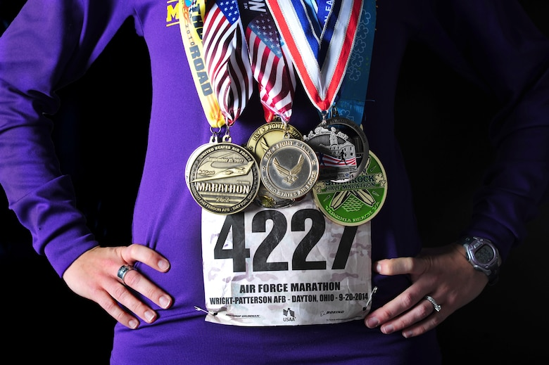 Second Lt. Abigail Webber wears her 2014 Air Force marathon bib number and medals from past half and full marathons, Nov. 19, 2014, at Langley Air Force Base, Va. Webber has run competitively since she joined her seventh grade cross country team at age 13. She is a 633rd Inpatient Squadron labor and delivery nurse. (U.S. Air Force photo/Staff Sgt. Natasha Stannard)