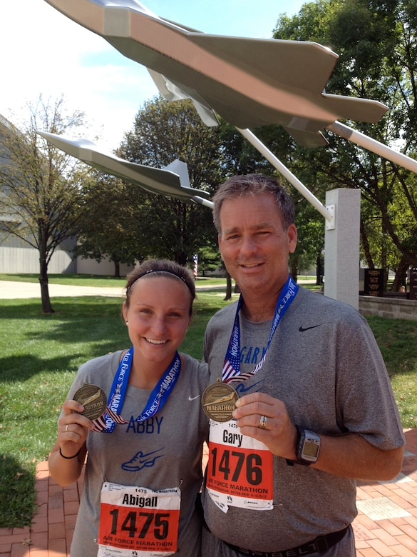 Second Lt. Abigail Webber poses for a photo with her father, retired Col. (Dr.) Gary Frederickson, after running the 2012 Air Force Marathon at Wright-Patterson Air Force Base, Ohio. Webber continues to run with her dad every week at her current duty station, Langley Air Force Base, Va. Webber is a 633rd Inpatient Squadron labor and delivery nurse. (U.S. Air Force courtesy photo)