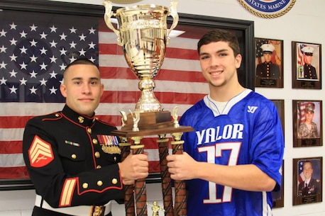 Austin Pinto, a senior at Connetquot High School, is presented the Dan Daly Cup trophy by Sgt. Eric Tirado, recruiter at Marine Corps Recruiting Substation Smithtown, at Connetquot High School Nov.18. Pinto represented his school in the Inaugural Dan Daly Cup all-star lacrosse game in June 2014. The trophy will be displayed in the high school from Nov. 18 until Dec. 1.