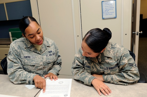 Senior Airman Ernestine Curtis, 30th Comptroller Squadron lead defense travel administrator, provides financial assistance to Airman 1st Class Vapsi Rubio, 30th Force Support Squadron personnel, Nov. 28, 2014, Vandenberg Air Force Base, Calif. With more than 130 different career fields in the Air Force, many Airmen find themselves much closer to a desk, in key support roles, than to the cockpit of an aircraft. (U.S. Air Force photo by Senior Airman Shane Phipps/Released)
