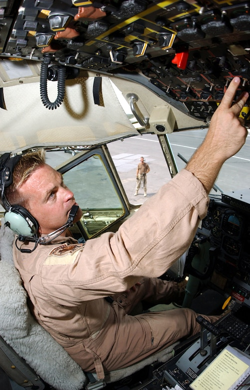 Master Sgts. Tom Rutt (foreground) and Scott Nybakken work in unison at a forward-deployed location in Southwest Asia ensuring a C-130 Hercules is ready for an airlift mission to Iraq on July 8, 2003. Rutt, a flight engineer, and Nybakken, a crew chief, are both assigned to the Delaware Air National Guard's 166th Airlift Wing. (U.S. Air Force photo by Master Sgt. Terry L. Blevins)