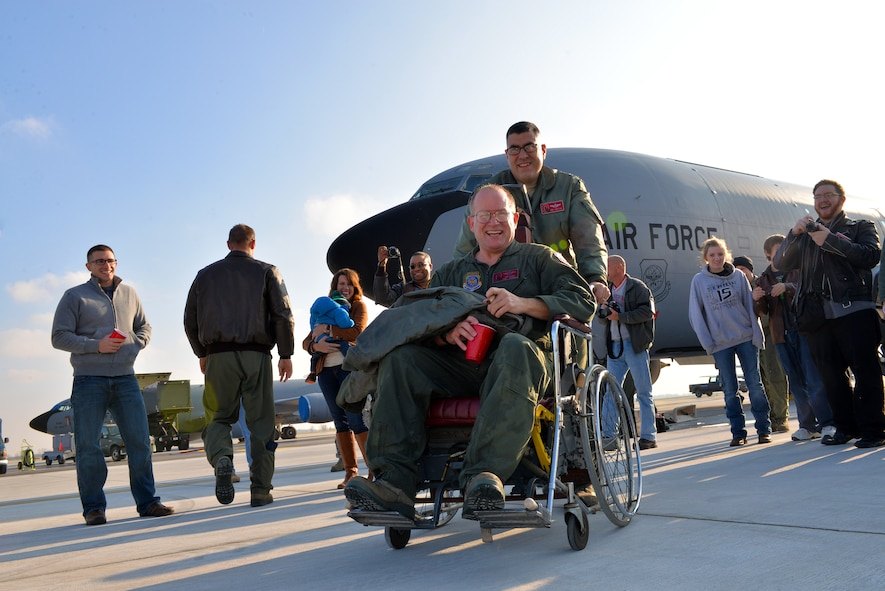 Chief Master Sgt. Tom Guard, a boom operator in the 121st Air Refueling Wing, gets a ride in a wheelchair from Lt. Col. Joe Contino Nov. 26, 2014, at Rickenbacker Air National Guard Base, Ohio. Guard had just completed his final flight after 41 years of service. (U.S. Air National Guard photo by Master Sgt. Ralph Branson/Released)