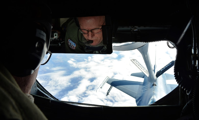 Chief Master Sgt. Tom Guard, a KC-135 Stratotanker boom operator in the 121st Air Refueling Wing, refuels an F-16 Fighting Falcon from the 180th Fighter Wing, Ohio in the skies over Ohio Nov. 26, 2014. Guard was taking his final flight after 41 years of service in the military and is set to retire on Dec. 19, 2014. (U.S. Air National Guard photo by Master Sgt. Ralph Branson/Released)