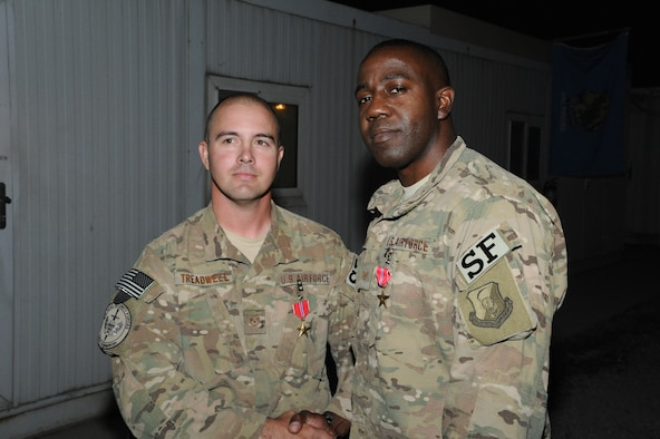 U.S. Air Force Tech. Sgts. Matthew Treadwell and Randy Sampson, both combat arms advisors for NATO Air Training Command  – Afghanistan, shake hands after being presented the Bronze Star with Valor. Treadwell is stationed at Altus Air Force Base, Okla., and Sampson is stationed at Travis Air Force Base, Calif. (Courtesy Photo)