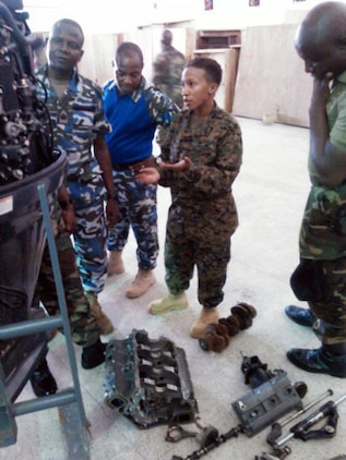 Petty Officer 2nd Class Angel Leonard shows service members with the Nigerian Navy various outboard motor parts during a training engagement in Nigeria, Dec. 2, 2014. Leonard, a Coast Guardsmen with SPMAGTF Crisis Response-Africa is working alongside service members of the Nigerian Navy for a training engagement that began in December. This training engagement will cover basic maintenance, electrical and mechanical skills, and general troubleshooting for small boat engines; the service members will share knowledge of these topics to build operational capacity between the two forces.