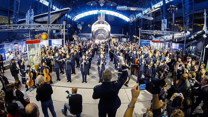 The United States Air Force Band performs a holiday flash mob Dec. 2, 2014, at the Smithsonian National Air and Space Museum Udvar-Hazy Center in Chantilly, Va. The band's mission is to honor those who have served, inspire American citizens to heightened patriotism and service, and positively impact the global community on behalf of the U.S. Air Force and America. (U.S. Air Force photo/Staff Sgt. Devon Suits)