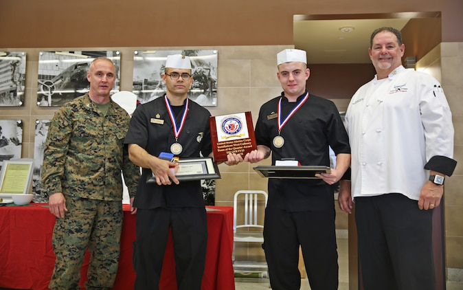 Sgt. Hugo P. Zepeda and Lance Cpl. Justin Gordon, food service specialists with Headquarters Squadron, Marine Corps Air Station Yuma, pose for a photograph with Col. Jeff Arruda, left, chief-of-staff, Marine Corps Base Camp Pendleton, Marine Corps Installations-West and Donovan Brown, right, head chef with Sodexo, after taking first place honors at the MCI-West Chef of the Quarter culinary competition here, Dec. 3.